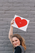 woman holding a picture of a heart that says hello