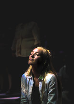 light on the face of a young woman in prayer