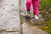 a toddler stepping in a mud puddle