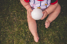 infant boy holding a baseball