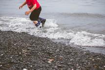 child in rain boots splashing in the ocean