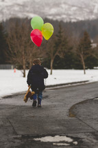 boy child walking outdoors in the snow carrying a teddy bear and balloons