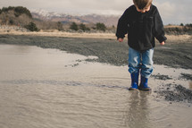 boy child in rain boots splashing in a puddle