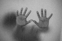 child's hands pressed against wet glass