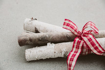 Birch logs tied with a red and white ribbon.