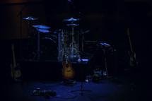drum set, symbols, and guitar on stage