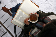 a woman reading a Bible outdoors in winter snow and has a tea cup