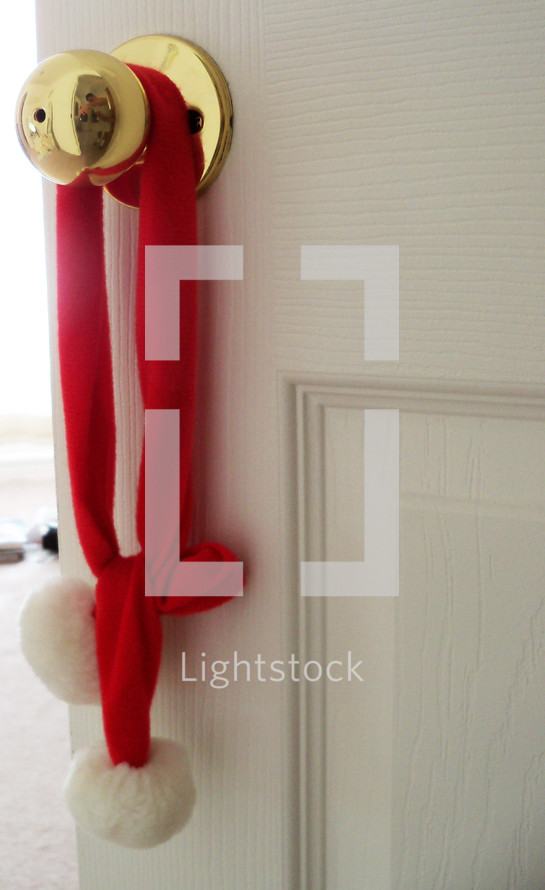 A bright and shiny brass doorknob decorated with red and white Christmas  decorations to add warmth, color and the spirit of the Christmas holidays to a room.