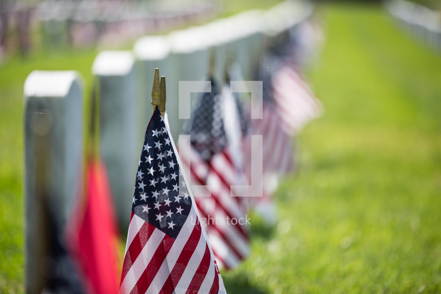 American flags at grave markers at a Veteran's Cemetery