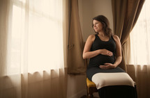 pregnant woman sitting in a chair holding her belly looking out a window