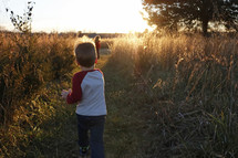 children running in a field at sunset