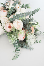 a bouquet of roses with eucalyptus