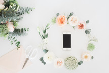 wreath of flowers around a cellphone, scissors, envelope, and bouquet of flowers