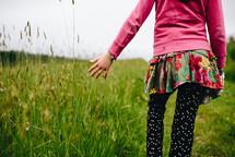 girl walking through tall green grasses