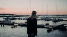 a young woman standing in a marina at dusk