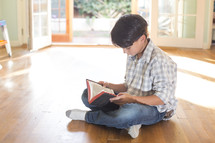 A child sitting on the floor and reading the Bible.