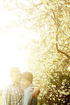 Couple embracing by flowering trees with sunbeams in background.