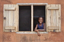 A little girl smiles from a window {Also try search for 'Ethnic Faces'}