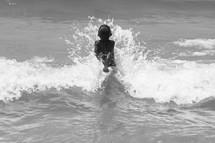 Boy splashing in the waves of the ocean