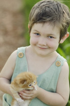 toddler holding cat - outdoors