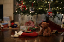 presents, stockings, and teddy bear under a Christmas tree