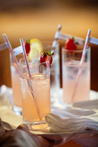 straws in glasses of strawberry lemonade
