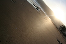 sideways view of sunset over sand on a beach