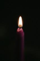 A purple Advent candle lit