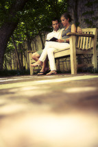 Couple reading Bible on park bench