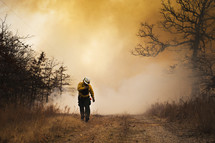 firefighter walking in front of smoke from a forest fire