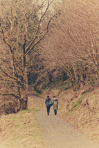 2 woman walking down country path through trees
