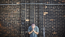 Man praying in front of brick wall
