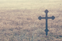 a metal cross in a field