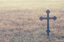a metal cross in a field