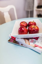 Bowl of red apples on table with magazines