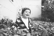 Smiling toddler boy sitting in the leaves