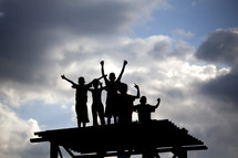 Silhouette of children with arms raised on top of platform.