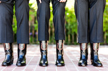 three men standing side by side in black cowboy boots