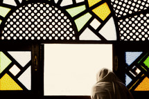 shrouded woman looking out stained glass windows