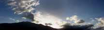 panoramic view of the sun breaking through clouds over mountains
