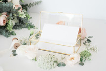 glass box with stationary and a border of roses
