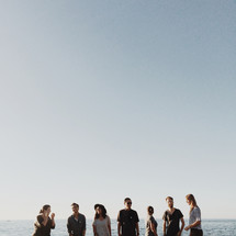 men and women standing outdoors in front of a view of the ocean