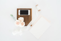 roses, cellphone, wood tray, spool of ribbons, and stationary
