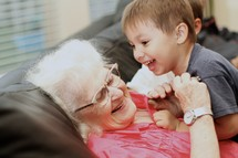 Young boy and grandmother laughing on couch