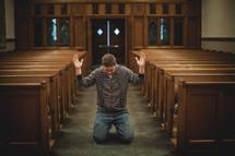 man kneeling in prayer with hands raised