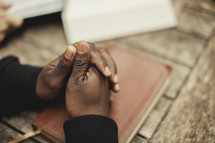 man with his hands folded in prayer over a Bible