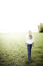 A woman walks toward the light