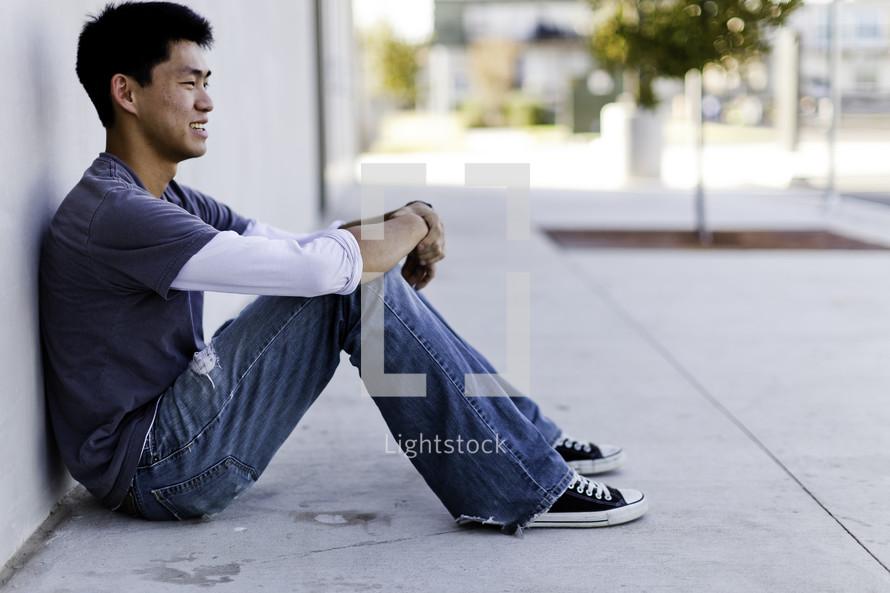 profile of a man sitting on a sidewalk
