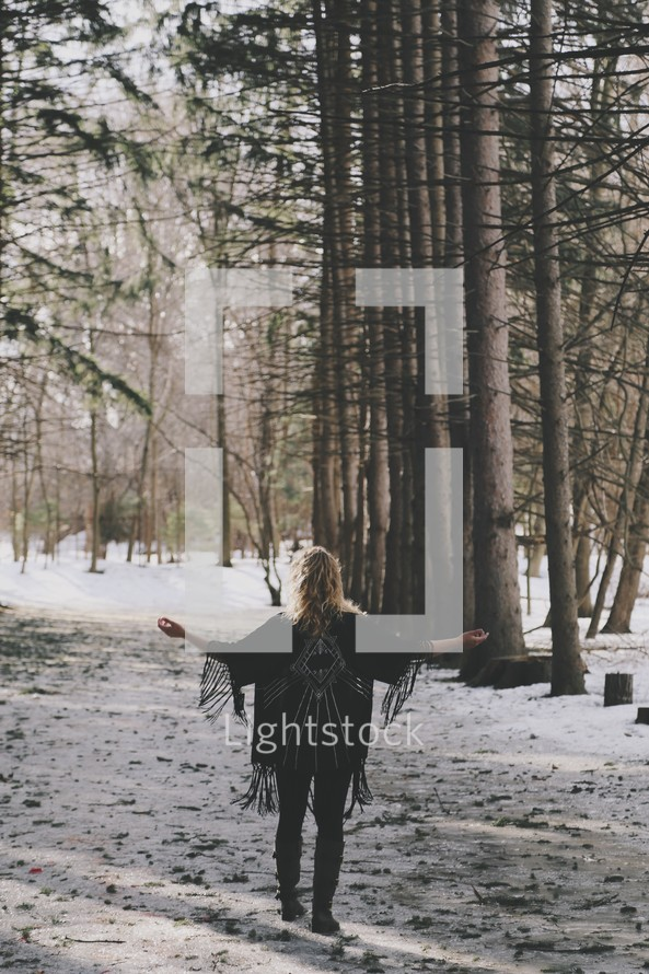 a woman standing with outstretched arms in a snowy forest