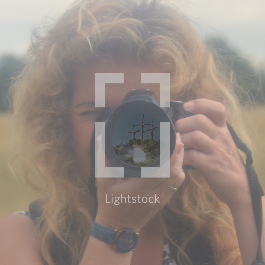 a woman taking a picture with a camera and three crosses in focus in the lens